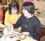 視覚障害者の手を取ってお皿の位置の確認をする